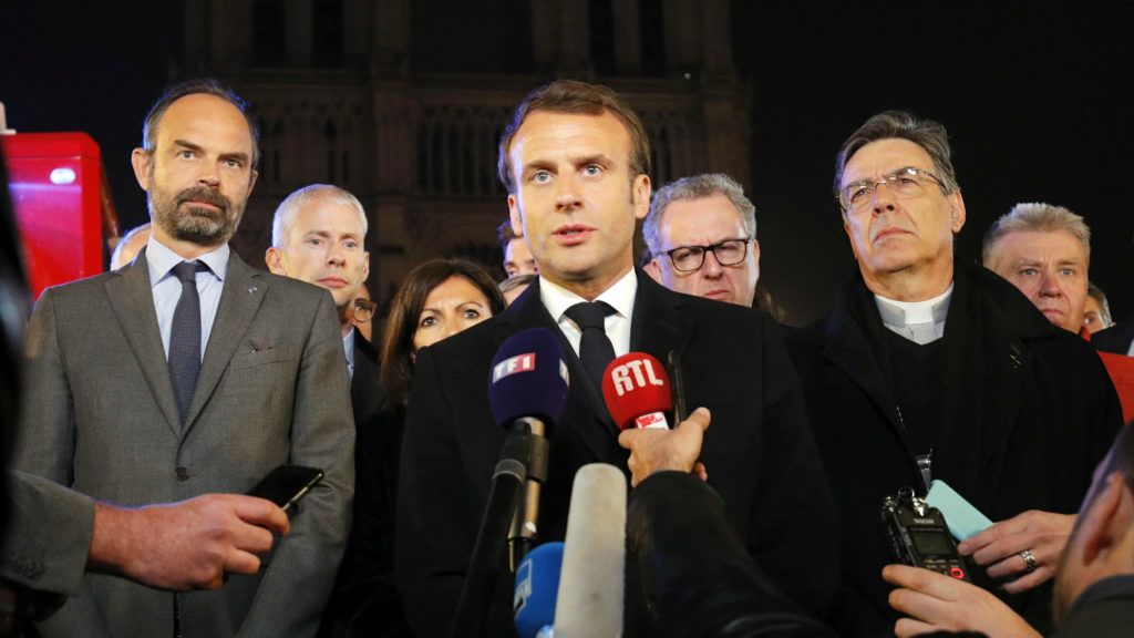 French President Emmanuel Macron (C) is accompanied by Mayor of Paris Anne Hidalgo (3L), French Prime Minister Edouard Philippe (L) French Culture Minister Franck Riester (2L) and Archbishop of Paris Michel Aupetit as he speaks at Notre-Dame Cathedral in Paris on April 15, 2019, after a fire engulfed the building. - A fire broke out at the landmark Notre-Dame Cathedral in central Paris, potentially involving renovation works being carried out at the site, the fire service said.Images posted on social media showed flames and huge clouds of smoke billowing above the roof of the gothic cathedral, the most visited historic monument in Europe. (Photo by PHILIPPE WOJAZER / POOL / AFP)