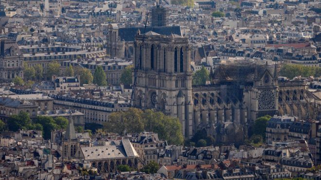 This picture taken from the Montparnasse tower on April 16, 2019 shows the landmark Notre-Dame de Paris Cathedral three days after a fire engulfed the 850-year-old gothic masterpiece, destroying the roof and causing the steeple to collapse in the center of the French capital Paris. - A major fire broke out at the landmark Notre-Dame Cathedral in central Paris sending flames and huge clouds of grey smoke billowing into the sky. The flames and smoke plumed from the spire and roof of the gothic cathedral, visited by millions of people a year, where renovations are currently underway. (Photo by Lionel BONAVENTURE / AFP)