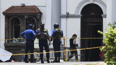 A foreign investigator (R) walks into St. Anthony's Shrine as soldiers stand guard in Colombo on April 25, 2019, following a series of bomb blasts targeting churches and luxury hotels on the Easter Sunday in Sri Lanka. - All of Sri Lanka's Catholic churches have been ordered to stay closed and suspend services until security improves after deadly Easter bombings, which killed at least 359 people and wounded hundreds, a senior priest told AFP on April 25. (Photo by Jewel SAMAD / AFP)
