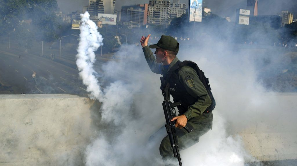 A member of the Bolivarian National Guard supporting Venezuelan opposition leader and self-proclaimed acting president Juan Guaido throws a tear gas canister during a confrontation with guards loyal to President Nicolas Maduro's government in front of La Carlota military base in Caracason April 30, 2019. - Guaido said on Tuesday that troops had joined his campaign to oust President Nicolas Maduro as the government vowed to put down what it called an attempted coup. (Photo by Yuri CORTEZ / AFP)