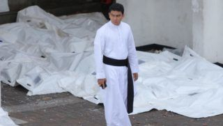A Sri Lankan catholic priest walks besides the dead bodies in front of the St Anthony's Church where an explosion took place in Kochchikade, Colombo, Sri Lanka, on April 21, 2019.- At least 200 people were killed in Sri Lanka on April 21 when a string of blasts ripped through high-end hotels and churches as worshipers attended  (Photo by Tharaka Basnayaka/NurPhoto)