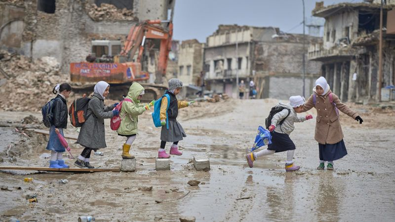 Girls navigate a muddy street as they make their way to school amid the rubble of the Old City of Mosul, Iraq, which was devastated during the 2017 Battle of Mosul, which led to the defeat of the Islamic State group, also known as ISIS. During control of the city by the Islamic State, most children didn't attend school.