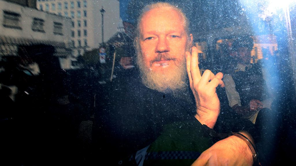 LONDON, ENGLAND - APRIL 11: Julian Assange gestures to the media from a police vehicle on his arrival att Westminster Magistrates court on April 11, 2019 in London, England.  After weeks of speculation Wikileaks founder Julian Assange was arrested by Scotland Yard Police Officers inside the Ecuadorian Embassy in Central London this morning. Ecuador's President, Lenin Moreno, withdrew Assange's Asylum after seven years citing repeated violations to international conventions. (Photo by Jack Taylor/Getty Images)