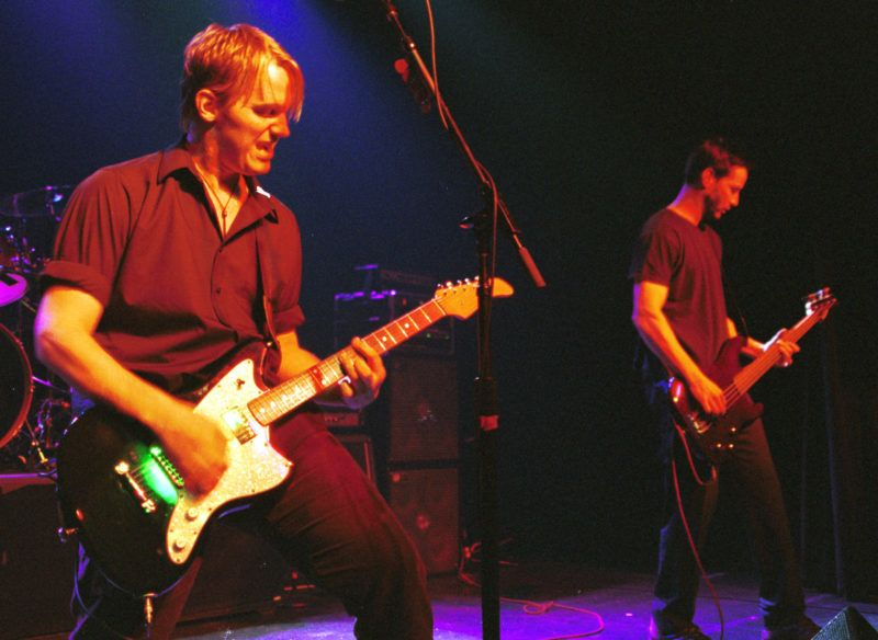 """372438 05: The rock band """"Dogstar"""" with members Bret Domrose on vocals and guitar (left) and actor Keanu Reeves on bass (right) perform at Irving Plaza July 7, 2000 in New York City. (Photo by George De Sota/Liaison)"""