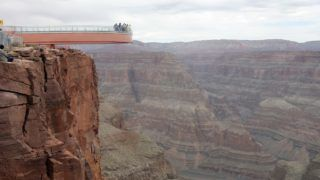 Astronaut Buzz Aldrin and other VIP guests make the ceremonial first steps on the Skywalk at Grand Canyon West on the Hualapai Indian Reservation in Arizona, 20 March 2007. The USD 30 million glass-bottomed walkway juts out 70 feet from the rim at an evelation of 4000 feet above the Colorado River.  The Hualapai tribe hopes this one-of-a-kind attraction will lure tourists to the remote area approximiately 2,5 hours from Las Vegas by car. (Photo by ROBYN BECK / AFP)