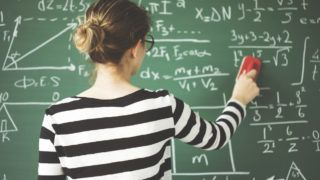Young student cleaning green chalkboard with duster  in classroom