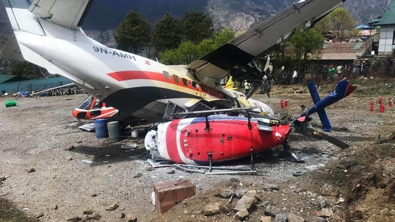 A Summit Air Let L-410 Turbolet aircraft bound for Kathmandu is seen after it hit two helicopters during take off at Lukla airport, the main gateway to the Everest region. - A small plane veered off the runway and hit two helicopters while taking off near Mount Everest on April 14, killing three people and injuring three, officials said. (Photo by STR / AFP)