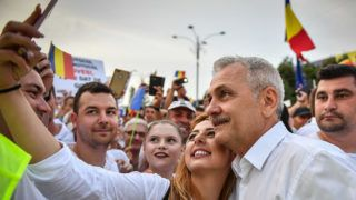Romania's social democratic party (PSD) leader Liviu Dragnea (2nd R) poses for a selfie with a supporter at the Piata Victoriei square, next to the Romanian Government headquarters, during a support meeting organized by the PSD (Social Democrat Party) ruling party in Bucharest, June 9, 2018. - From busing supporters to Bucharest to mass mailings of party slogans, Romania's left-wing government was pulling out all the stops for the demonstration against the country's own judiciary. (Photo by Daniel MIHAILESCU / AFP)