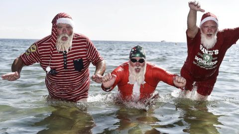 Actors dressed as Santa Claus take a refreshing bath at Bellevue Beach north of Copenhagen, Denmark, on July 24, 2018, as they take part in the World Santa Congress, an annual two-day event held every summer in Copenhagen. (Photo by Mads Claus Rasmussen / Ritzau Scanpix / AFP) / Denmark OUT