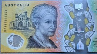 """This photo illustration shows the detail in Australia's state-of-the-art new 50 dollar banknote in Sydney on May 9, 2019, with a spelling mistake in the microprint of a speech by Australia's first woman parliamentarian Edith Cowan. - The yellow and green note came into circulation last October, but it took seven months for the public to notice """"responsibility"""" was repeatedly misspelt in the text of Cowen's maiden speech to Australia's parliament in July 1921. (Photo by Peter PARKS / AFP) / --- RESTRICTED TO EDITORIAL USE ---"""