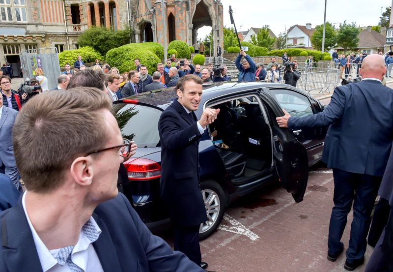 French President Emmanuel Macron (C) gestures as he leaves a polling station in Le Touquet, northern France, on May 26, 2019, after voting in European parliamentary elections. (Photo by PHILIPPE HUGUEN / AFP)