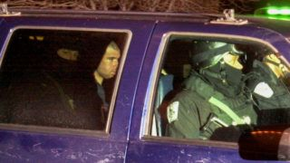 US-Taliban fighter John Walker Lindh (2nd-L) rides in the back seat with security officers 23 January, 2002, as they arrive at the Alexandria Detention Center in Alexandria, Virginia. Walker, the US national accused of fighting for the Taliban in Afghanistan against US-backed troops, is to appear 24 January before US Magistrate Judge Weldon Sewell in the district court on charges of conspiring to kill US nationals and supporting terrorist groups, said Paul McNulty, US attorney for the eastern district of Virginia. Walker was captured in northern Afghanistan in November and then survived a bloody uprising by Taliban and al-Qaeda prisoners at a fort near Mazar-i-Sharif before coming to the attention of US authorities. He faces life in prison if convicted on the conspiracy charge.   AFP PHOTO/ Shawn THEW (Photo by SHAWN THEW / AFP)
