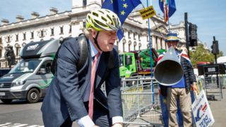 Pro-Brexit Conservative MP Boris Johnson rides his bicycle as he arrives at the Houses of Parliament in London on May 15, 2019. (Photo by Tolga AKMEN / AFP)