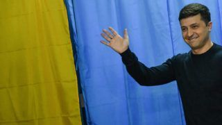 (FILES) In this file photo taken on March 31, 2019 Ukrainian comic actor, showman and then presidential candidate Volodymyr Zelensky waves in front of voting booths at a polling station during Ukraine's presidential election in Kiev. - Ukraine's parliament voted on May 16, 2019 to hold the inauguration of the newly elected president, comedian Volodymyr Zelensky, on May 20, 2019, after he wrangled with lawmakers over the date. (Photo by GENYA SAVILOV / AFP)