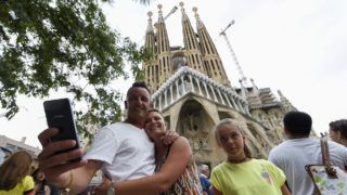 """Tourists pose for selfies in front of the """"Sagrada Familia"""" (Holy Family) basilica in Barcelona on August 19, 2017, two days after a van ploughed into the crowd, killing 13 persons and injuring over 100. - Drivers have ploughed on August 17, 2017 into pedestrians in two quick-succession, separate attacks in Barcelona and another popular Spanish seaside city, leaving 14 people dead and injuring more than 100 others. (Photo by LLUIS GENE / AFP)"""