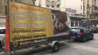 """An advertising board of the dating site """"RichMeetBeautiful"""" reading """"students, romantic, passion and no student loan, meet a Sugar Daddy or a Sugar Mama"""" is displayed in a street of Paris on October 25, 2017. - The advertising truck lauding a dating site near Paris universities and accused of inciting to """"prostitution"""" by the city, was seized for """"unauthorised display"""", said the Paris police prefecture on October 26, 2017 (Photo by Anais CAQUANT / AFP)"""