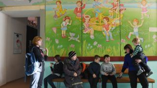 Children wait in a queue for vaccination against measles in a pediatric polyclinic in Kiev on January 15, 2018. - Schools have shuttered and some clinics exhausted their vaccine stocks as a deadly measles outbreak hits Ukraine, where anti-vaccine sentiment and interrupted supplies have led to a resurgence of the virus. Ukrainian authorities and international organisations blame the outbreak on a lengthy hiatus in immunisations, caused by public resistance to vaccines fanned by news reports and rumours. (Photo by Sergei SUPINSKY / AFP)