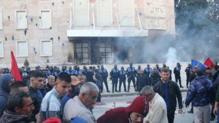 TIRANA, ALBANIA - MAY 11 :  Smoke rises from a building after protestors throw molotov bomb behind police officers during an anti-government rally in Tirana,Albania on May 11, 2019. Olsi Shehu / Anadolu Agency
