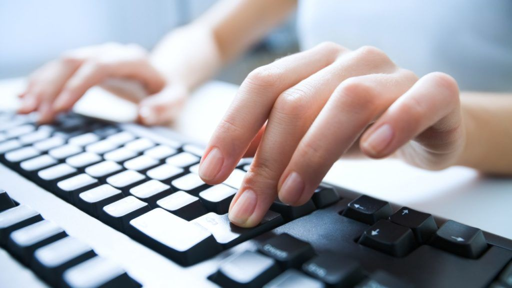 Close-up of female hand pressing enter key to start the system
