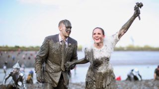 MALDON, ENGLAND - MAY 05:  A couple dressed as a bride and groom take part in the Maldon Mud Race on May 05, 2013 in Maldon, Essex. The race originated in 1973 and involves competitors racing around a course on the mudbanks of the river Blackwater at low tide.  (Photo by Dan Kitwood/Getty Images)