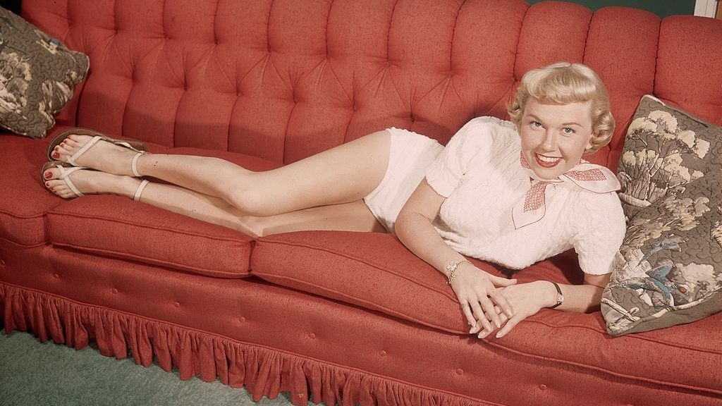 circa 1945:  Full-length portrait of American actor Doris Day reclining on a red couch and smiling.  Day is wearing a white leotard and a red and white scarf.  (Photo by Hulton Archive/Getty Images)