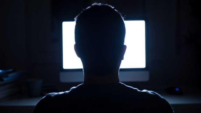 Silhouette of man's head in front of computer monitor light at night