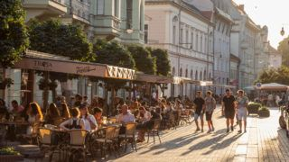 Picture of young white caucasian males walking in the pedestrian streets at sunset, while people are sitting at the tables of bars and cafes nearby, in the city of Szeged, hungary. This city is the 3rd largest city of Hungary, the largest city and regional centre of the Southern Great Plain and the county seat of Csongrad county