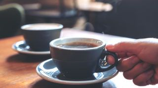 Closeup image of a hand holding a blue cup of hot coffee with smoke on wooden table in cafe