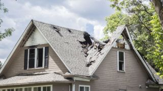 horizontal close up image of a roof of a house that has burned and fallen in under blue sky with cloud in summer time.