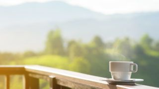 White cup of hot coffee on balcony with natural and mountains, hills background. copy space.