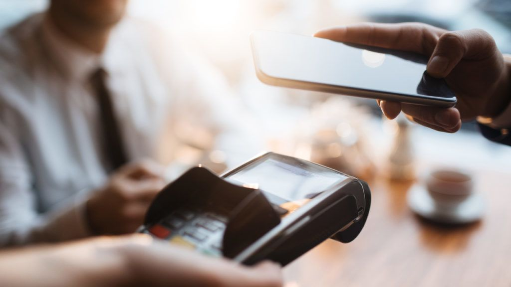 Buyer with smartphone paying through terminal