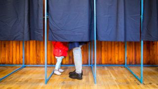 People vote in a voting booth at a polling station.