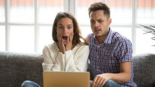 Shocked couple feeling confused and scared while watching horror scary film video movie online, worried young family sitting on sofa together looking at laptop screen with surprise or bewilderment