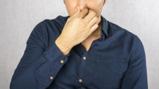 Cover nose gesture by man on grey background
