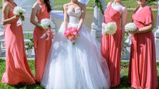 Beautiful bridesmaids and bride in bridal gown with bouquets in the nature. Beauty model girls in a colorful wedding dresses. Female portraits in the park. Women with hairstyle. Cute ladies outdoors