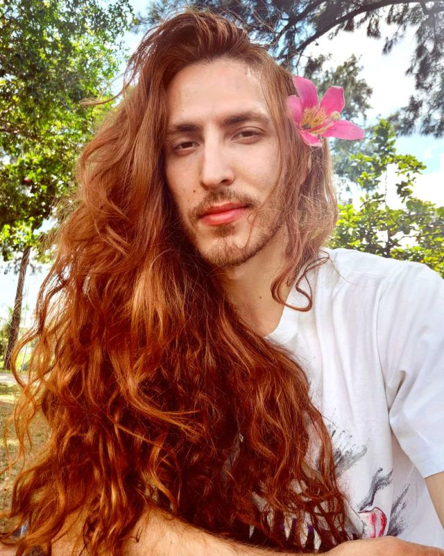 Cristiano posing with a flower in his long hair. MEET THE man who has been growing his hair for SEVEN YEARS and plans to keep it long despite being called an 'ugly woman' and has even been accused of TURNING women's SEXUALITY. Actor and model, Cristiano Braga (28), from Minas Gerais, Brazil, has been growing his long hair since 2012 when he decided to take the plunge, despite feeling hesitant in case he got bullied at school. His striking look has attracted a lot of positive and negative attention, some from women who say it's 'unfair' for a man to have luscious locks like his and from men who accuse him of wanting to 'turn' women's sexuality due to his long hair. He has learned to brush off cruel trolls and says he is proud of his hair and treats it with care. He maintains it with natural oils such as aloe vera, avocado, camomile, mint, rosemary and vegetables. Despite his hair being two-foot-two in length, he says it only takes him five minutes to wash it and has been compared to Ariel from The Little Mermaid. mediadrumworld.com / Cristiano Braga ***EXCLUSIVE***