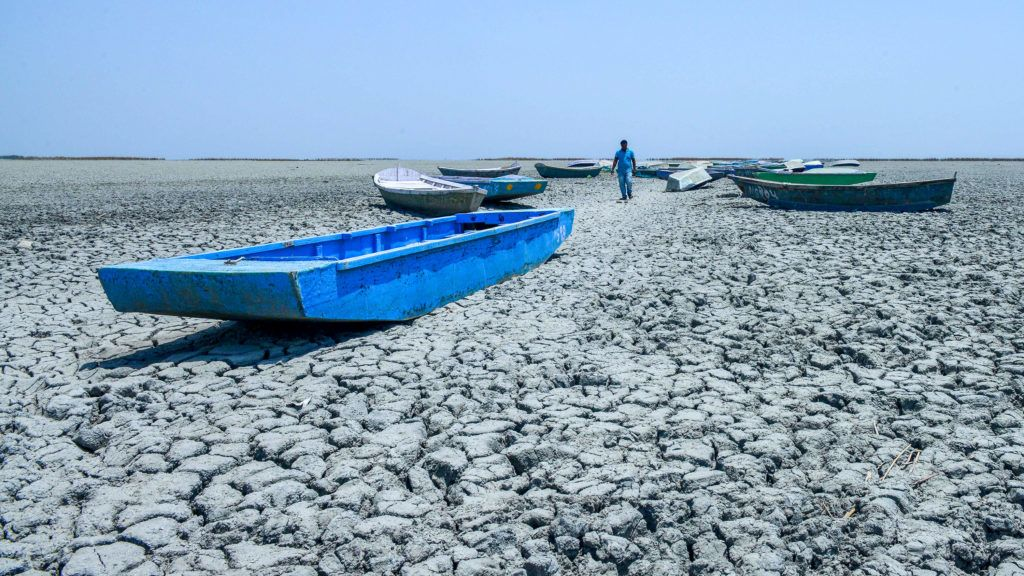 In this picture taken on June 4, 2019, an Indian boatman walks amid boats on the dried bed of a lake at Nalsarovar Bird Sanctuary, on the eve of World Environment Day. - Because of less monsoon rains last year and current heatwave conditions, the Nalsarovar Bird Sanctuary, which attracts thousands of migratory birds every year, has dried up. (Photo by SAM PANTHAKY / AFP)