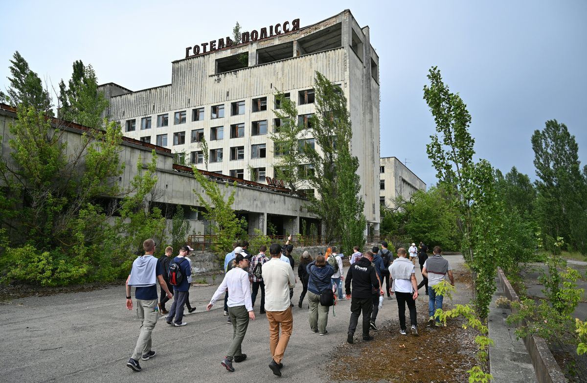 """Visitors walk in the ghost city of Pripyat during a tour in the Chernobyl exclusion zone on June 7, 2019. - HBO's hugely popular television series """"Chernobyl"""" has renewed interest around the world on Ukraine's 1986 nuclear disaster with authorities reporting a 30% increase of tourist demands to visit the affected area and tourist operators forecasting that number of tourists visiting the site may double this year up to 150.000 persons (Photo by Genya SAVILOV / AFP)"""