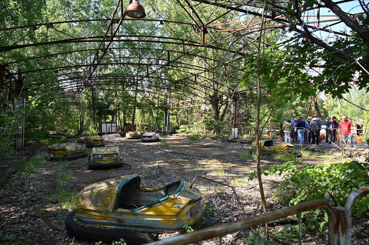 """Visitors walk in the ghost city of Pripyat during a tour in the Chernobyl exclusion zone on June 1, 2019. - HBO's hugely popular television series """"Chernobyl"""" has renewed interest around the world on Ukraine's 1986 nuclear disaster with authorities reporting a 30% increase of tourist demands to visit the affected area and tourist operators forecasting that number of tourists visiting the site may double this year up to 150.000 persons. (Photo by Genya SAVILOV / AFP)"""