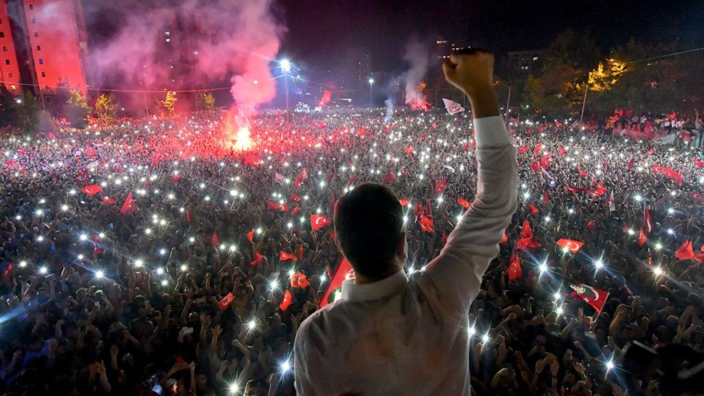 """A handout image taken on June 23, 2019 and made available on June 24, 2019 by the CHP Press office shows Republican People's Party (CHP) candidate for mayor of Istanbul Ekrem Imamoglu (C) celebrating in front of thousands of supporters at Beylikduzu in Istanbul on June 23, 2019. - Turkey's opposition revelled Monday in a landslide win in Istanbul's re-run mayoral vote -- a blow for President Recep Tayyip Erdogan that even some pro-government media called a victory for democracy. Ekrem Imamoglu, a little-known district mayor at the start of the year, won the election by more than 777,000 votes, up from just 13,000 in the first election in March, which was annulled over controversial claims of fraud. (Photo by Onur GUNAL / Republican People's Party (CHP) Press Service / AFP) / RESTRICTED TO EDITORIAL USE - MANDATORY CREDIT """"AFP PHOTO / Republican People's Party (CHP) / Onur GUNAL"""" - NO MARKETING - NO ADVERTISING CAMPAIGNS - DISTRIBUTED AS A SERVICE TO CLIENTS"""
