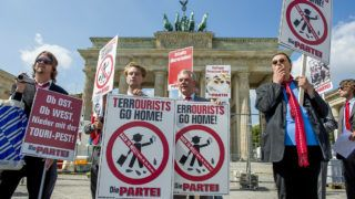 """Members of the satirical political party """"Die Partei"""" display placards urging """"Terrourists"""" to go home, during a protest at Berlin's Brandenburg Gate on August 15, 2013. The party, whose chairman Martin Sonneborn co-publishes Germany's best known satirical magazine Titanic, aims to liven up the otherwise dull parliamentary elections with campaign pledeges such as limiting management pay to 25,000 times an ordinary worker's pay, or building a wall around Germany to tackle globalization, financial market turmoil and the euro crisis. Placard on L reads: """"Whether from the Est ot the West, down with the tourists pests"""". AFP PHOTO / JOHN MACDOUGALL (Photo by JOHN MACDOUGALL / AFP)"""