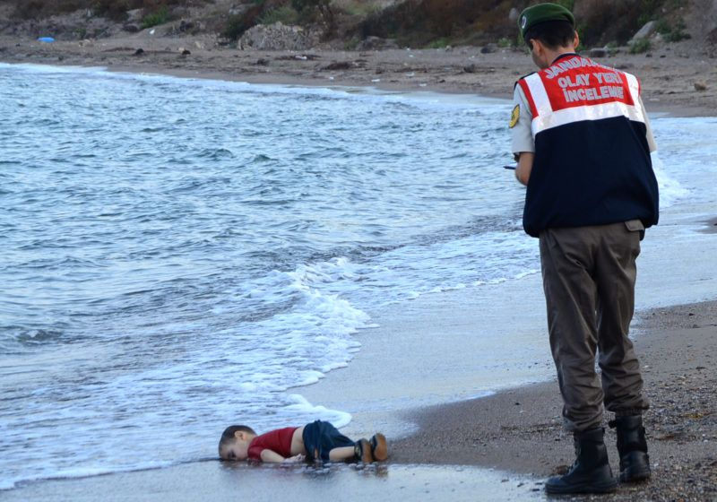 GRAPHIC CONTENT A Turkish police officer stands next to a migrant child's dead body (Aylan Shenu) off the shores in Bodrum, southern Turkey, on September 2, 2015 after a boat carrying refugees sank while reaching the Greek island of Kos. Thousands of refugees and migrants arrived in Athens on September 2, as Greek ministers held talks on the crisis, with Europe struggling to cope with the huge influx fleeing war and repression in the Middle East and Africa. (Photo by Nilufer Demir / DOGAN NEWS AGENCY / AFP)