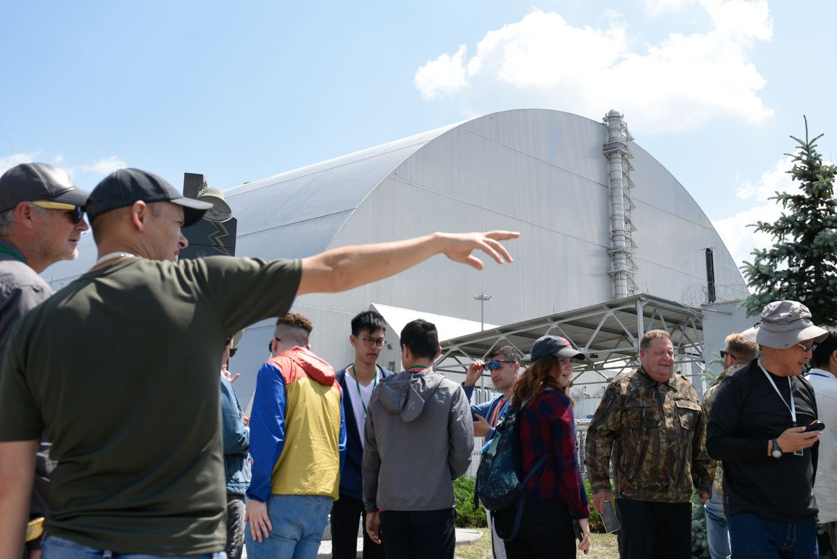 5914497 12.06.2019 Visitors stand outside the New Safe Confinement (NSC) structure over the old sarcophagus covering the damaged fourth reactor at the Chernobyl Nuclear Power Plant, Ukraine. The Chernobyl miniseries by HBO, which depicts aftermath of the world's worst nuclear accident occurred on April 26, 1986 at the Chernobyl Nuclear Power Plant, including the clean-up operation and subsequent inquiry, drives boom in tourists travelling to see the site of nuclear disaster. Stringer / Sputnik
