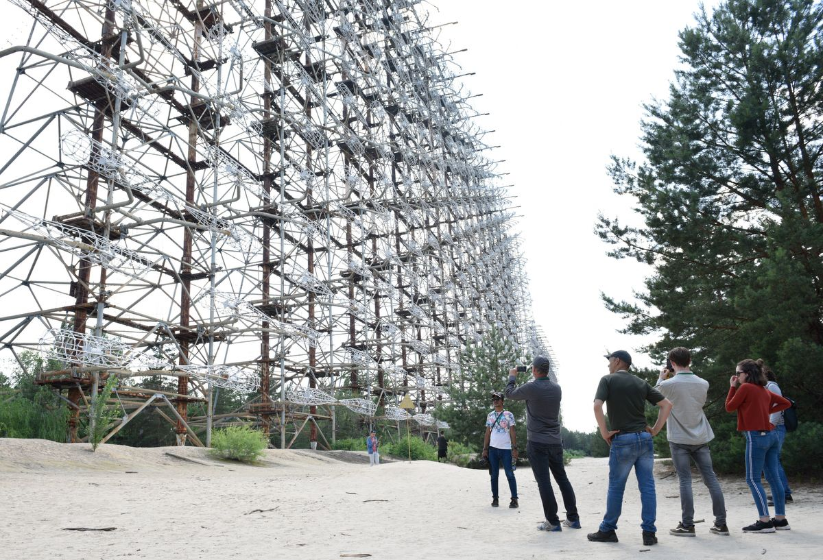 """5914513 12.06.2019 Visitors inspect constructions of a former Soviet Union over-the-horizon (OTH) radar system """"Duga"""" near the Chernobyl Nuclear Power Plant, near Chernobyl, Ukraine. The Chernobyl miniseries by HBO, which depicts aftermath of the world's worst nuclear accident occurred on April 26, 1986 at the Chernobyl Nuclear Power Plant, including the clean-up operation and subsequent inquiry, drives boom in tourists travelling to see the site of nuclear disaster. Stringer / Sputnik"""