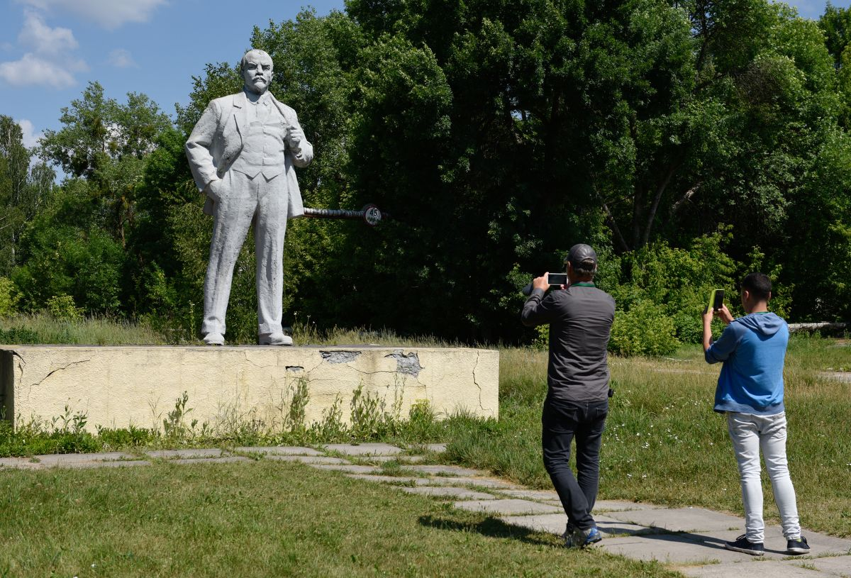 5914560 12.06.2019 Visitors take pictures of a statue to Soviet state founder Vladimir Lenin in the abandoned city of Pripyat, near the Chernobyl nuclear power plant, Ukraine. The Chernobyl miniseries by HBO, which depicts aftermath of the world's worst nuclear accident occurred on April 26, 1986 at the Chernobyl Nuclear Power Plant, including the clean-up operation and subsequent inquiry, drives boom in tourists travelling to see the site of nuclear disaster. Stringer / Sputnik