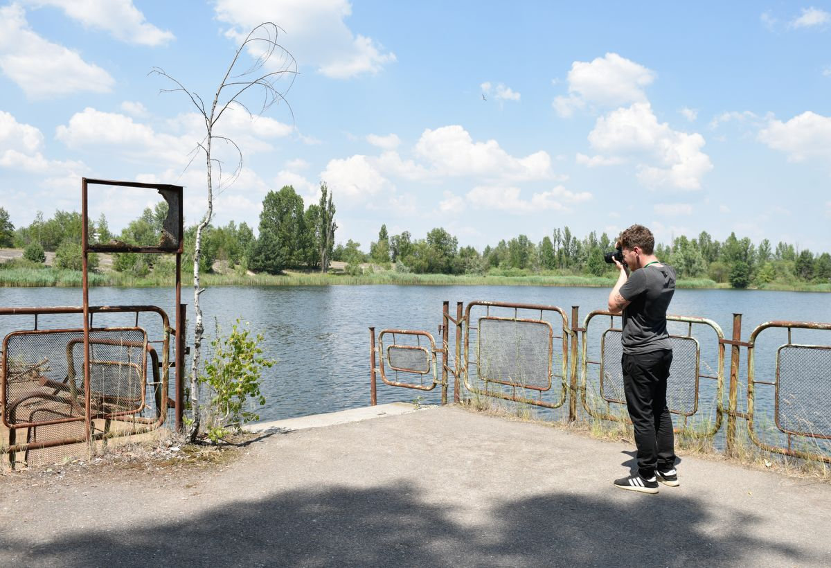 5914562 12.06.2019 A visitor takes pictures at a river port of the abandoned city of Pripyat, near the Chernobyl nuclear power plant, Ukraine. The Chernobyl miniseries by HBO, which depicts aftermath of the world's worst nuclear accident occurred on April 26, 1986 at the Chernobyl Nuclear Power Plant, including the clean-up operation and subsequent inquiry, drives boom in tourists travelling to see the site of nuclear disaster. Stringer / Sputnik