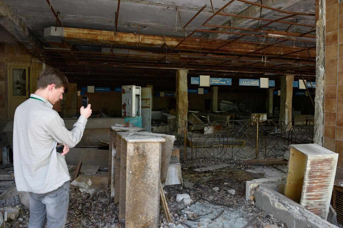 5914567 12.06.2019 A visitor takes pictures at a former grocery store building in the abandoned city of Pripyat, near the Chernobyl nuclear power plant, Ukraine. The Chernobyl miniseries by HBO, which depicts aftermath of the world's worst nuclear accident occurred on April 26, 1986 at the Chernobyl Nuclear Power Plant, including the clean-up operation and subsequent inquiry, drives boom in tourists travelling to see the site of nuclear disaster. Stringer / Sputnik