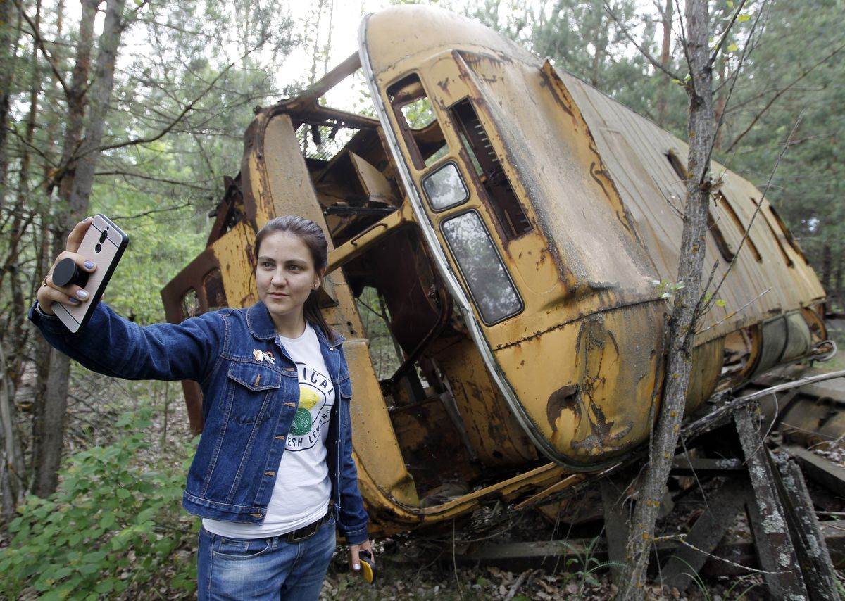 A visitor takes a selfie in front of a wreckage bus in the abandoned city of Pripyat, near the Chernobyl nuclear power plant, Ukraine, on 7 June 2019.The Chernobyl Series (HBO) , which depicts the Chernobyl nuclear power disaster's aftermath, including the clean-up operation and subsequent inquiry, drives boom in tourists travelling to see the site of nuclear disaster. Tour agencies have reported up to a 40 per cent increase in bookings since the miniseries aired May 2019. On 2019 Ukraine marked the 33rd anniversary of Chernobyl nuclear disaster. The Chernobyl accident occurred on 26 April 1986 at the Chernobyl Nuclear Power Plant near the city of Pripyat, and regarded the biggest nuclear accident in the history. (Photo by STR/NurPhoto)