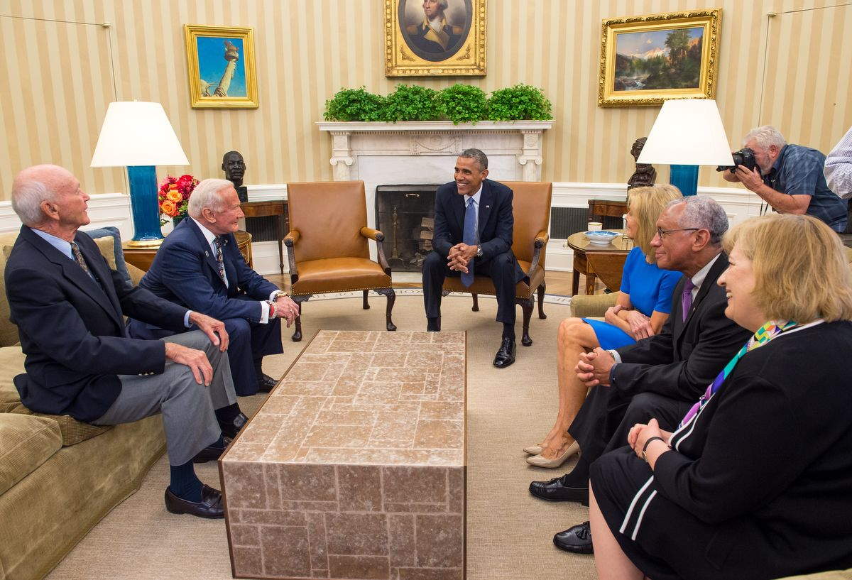 """President Barack Obama meets with Apollo 11 astronauts Michael Collins, seated left, Buzz Aldrin, Carol Armstrong, widow of Apollo 11 commander, Neil Armstrong, NASA Administrator Charles Bolden, and Patricia """"Pat"""" Falcone, OSTP Associate Director for National Security & International Affairs, far right, Tuesday, July 22, 2014, in the Oval Office of the White House in Washington, during the 45th anniversary week of the Apollo 11 lunar landing. Photo Credit: (NASA/Bill Ingalls)"""