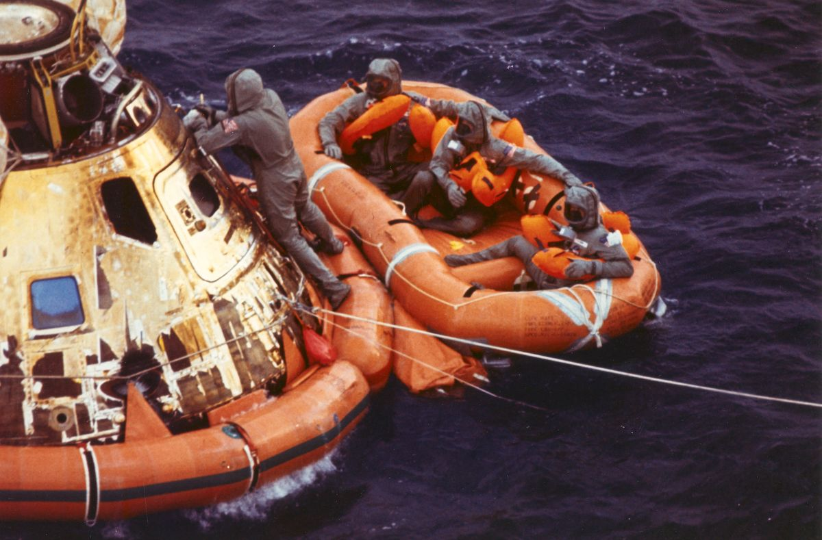 Pararescueman Lt. Clancy Hatleberg closes the Apollo 11 spacecraft hatch as astronauts Neil Armstrong, Michael Collins, and Buzz Aldrin, Jr., await helicopter pickup from their life raft. They splashed down at 12:50 pm EDT July 24, 1969, 900 miles southwest of Hawaii after a successful lunar landing mission.